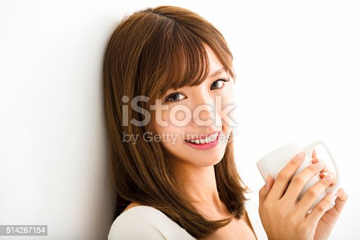 istock young Woman drinking hot latte coffee in living room 514267154