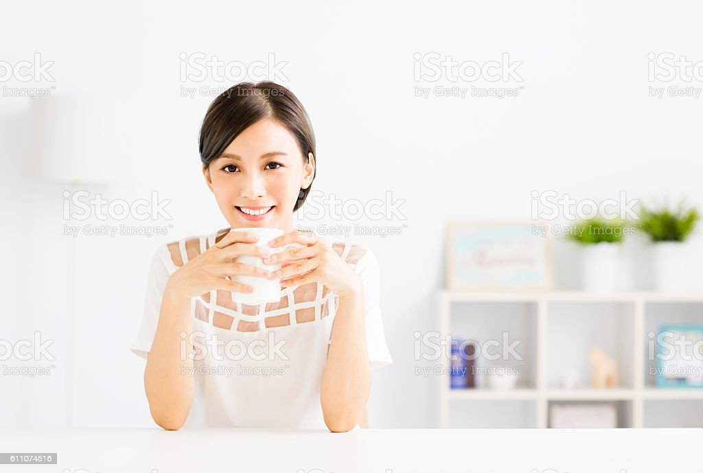young Woman drinking hot latte coffee in living room stock photo