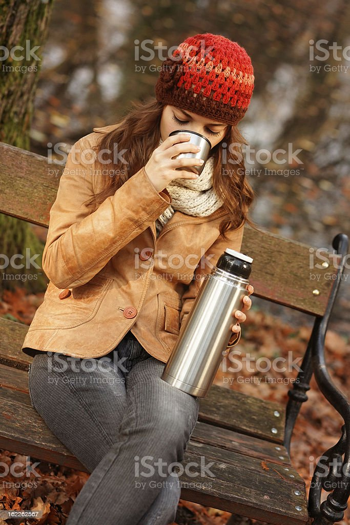 young woman drinking hot tea from thermos travel mug royalty-free stock photo
