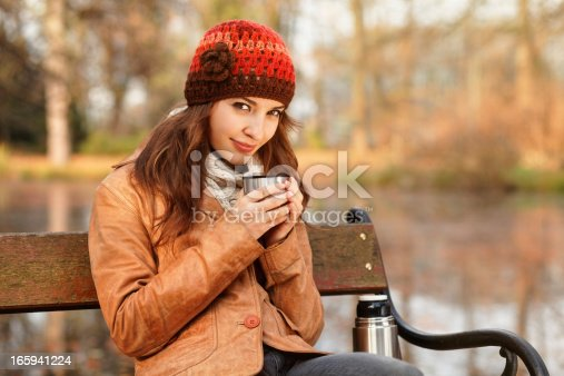 istock young woman drinking hot tea from thermos travel mug 165941224