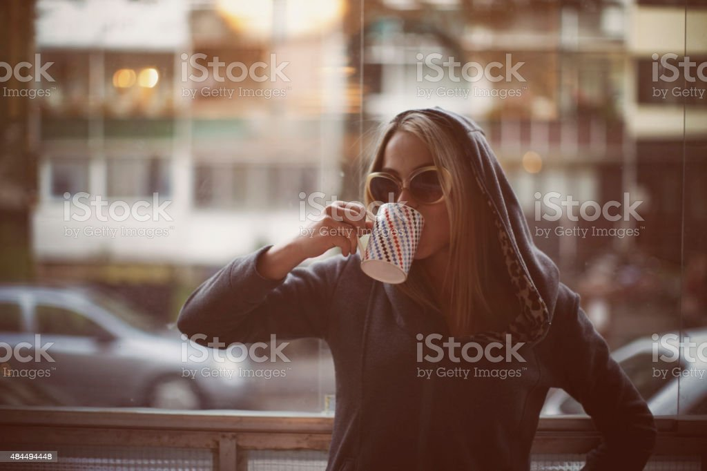 Young woman drinking late morning coffee stock photo
