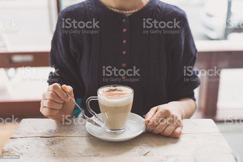 Young woman drinking latte in cafe stock photo