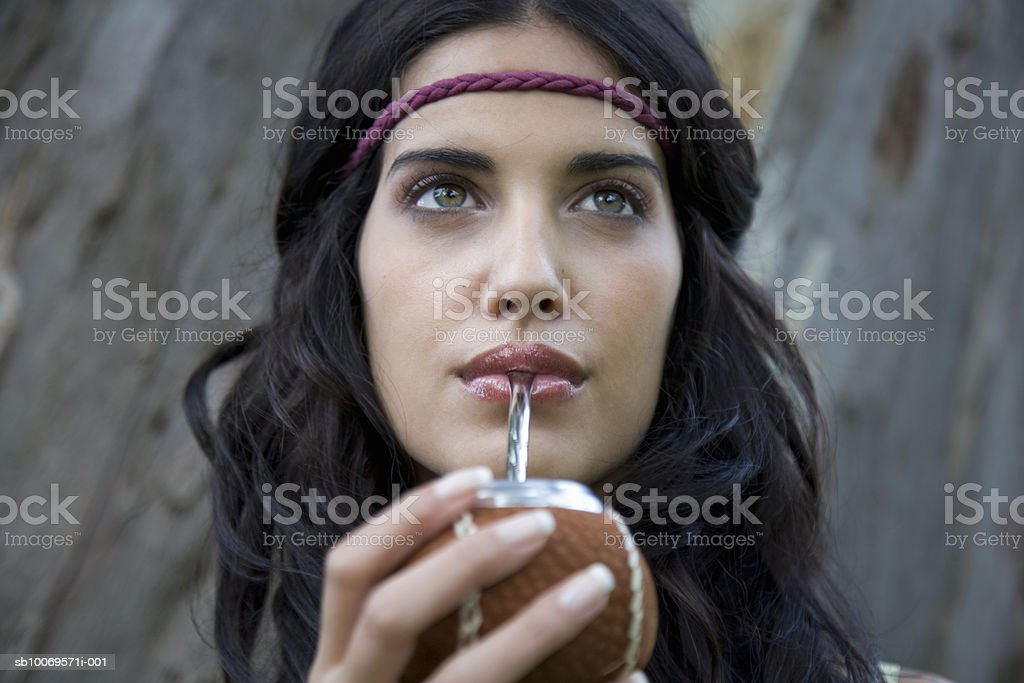 Young woman drinking mate from traditional cup, outdoors foto de stock libre de derechos