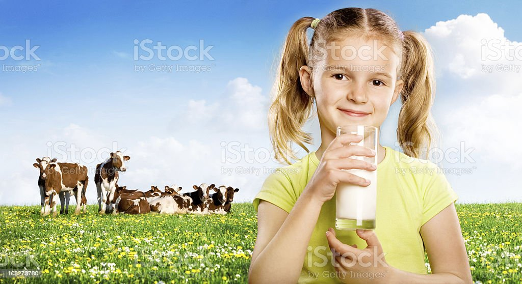 Young Woman Drinking Milk in Front of Field stock photo