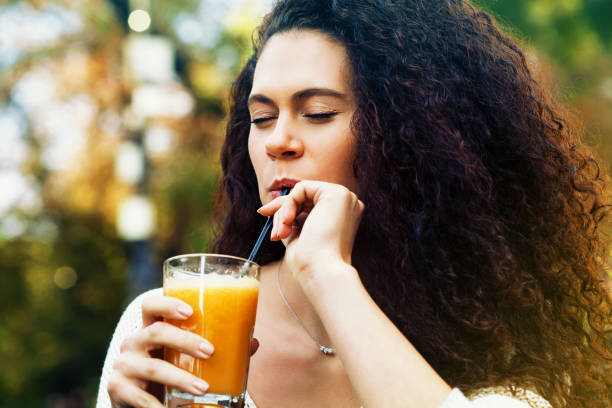 Young woman drinking orange juice stock photo