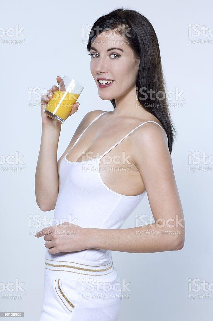 Giovane donna bere succo d'arancia foto stock royalty-free