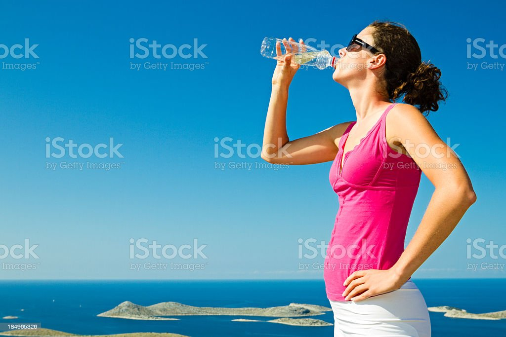 A young woman drinking out of a water bottle royalty-free stock photo