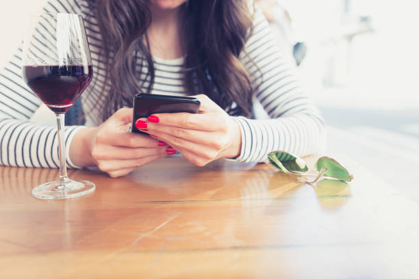 Young woman drinking red wine at restaurant, using smart phone stock photo