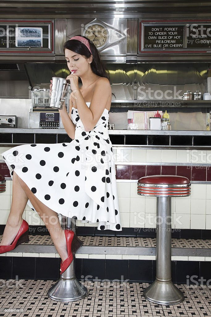 Young Woman Drinking Shake In Diner stock photo