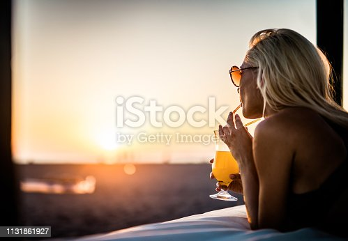 Young woman relaxing on a beach bed and enjoying in drink at sunset. Copy space.