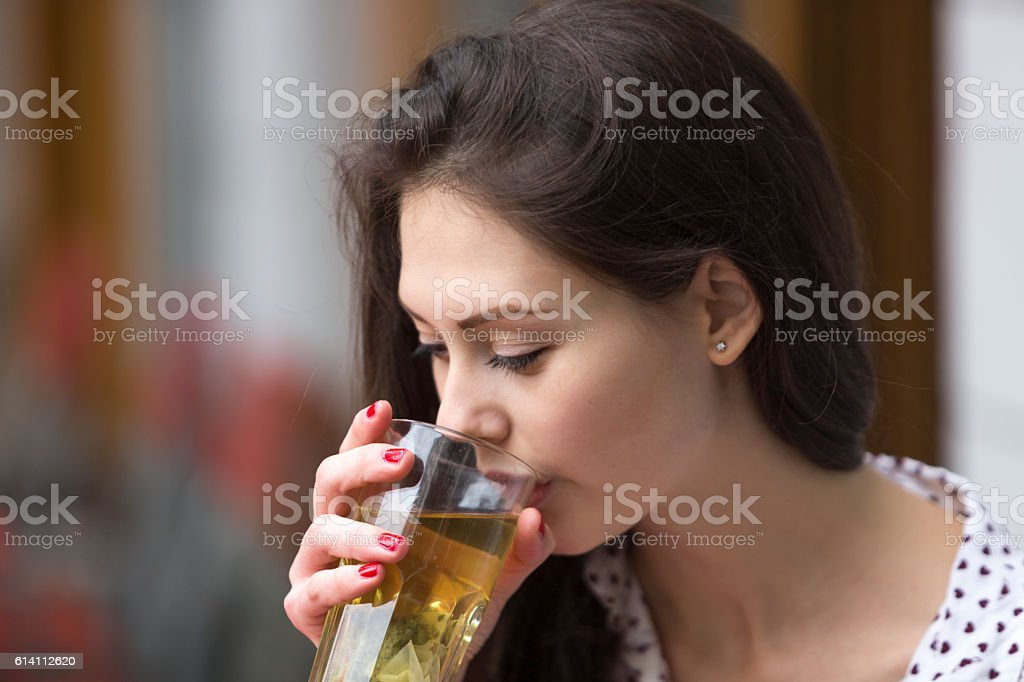Young woman drinking tea outide a coffee shop stock photo