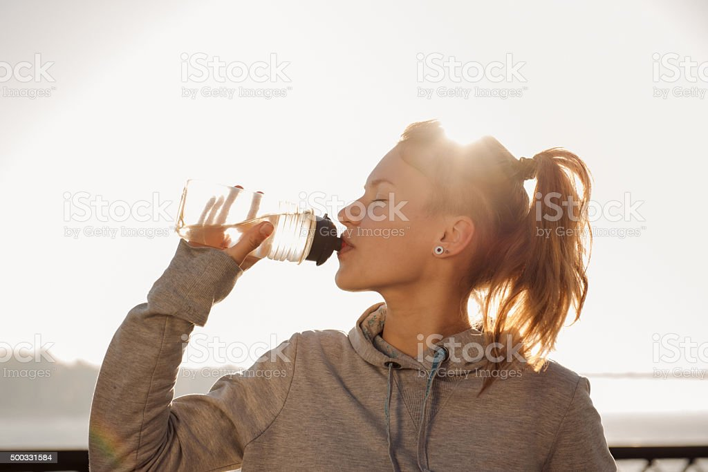Young woman drinking water after cycling stock photo