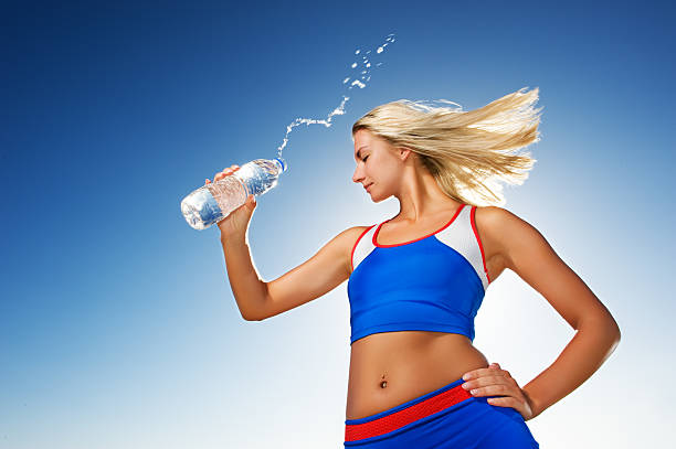 Young woman drinking water after fitness exercise stock photo