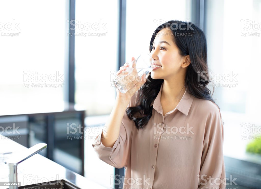 young woman drinking water in the kitchen at home - Royalty-free Adult Stock Photo