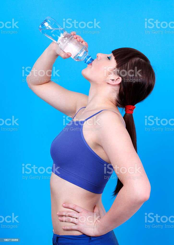 Young woman drinking water on blue background royalty-free stock photo