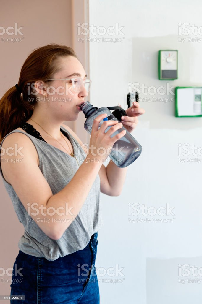 Young woman drinking water while painting living room. stock photo