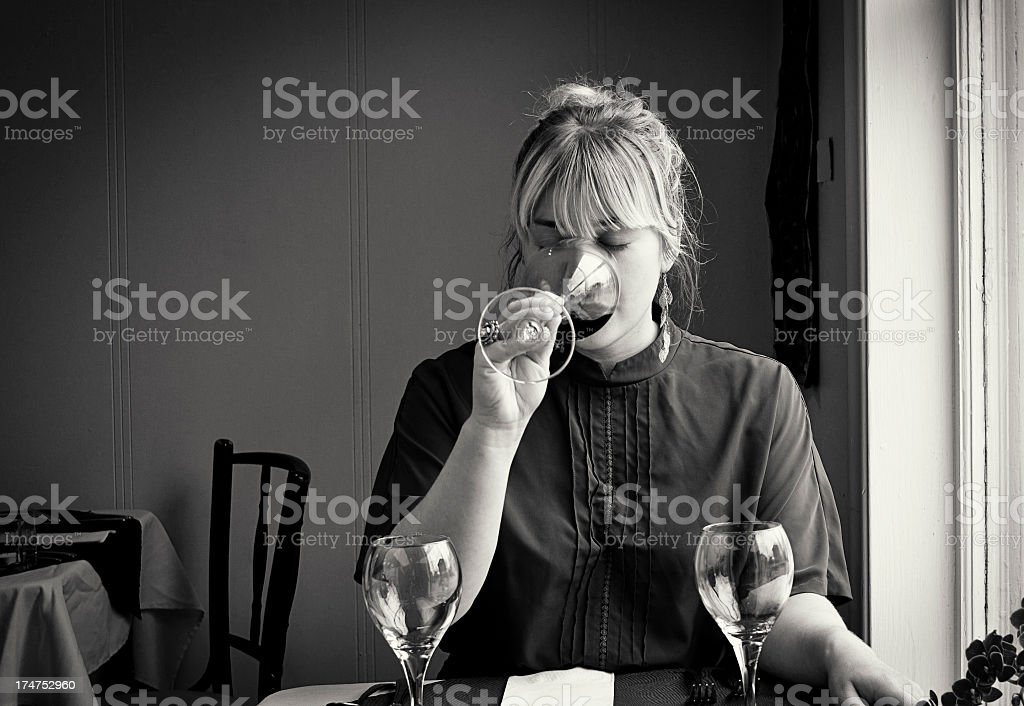 Young Woman Drinking Wine in a Cafe or Bistro