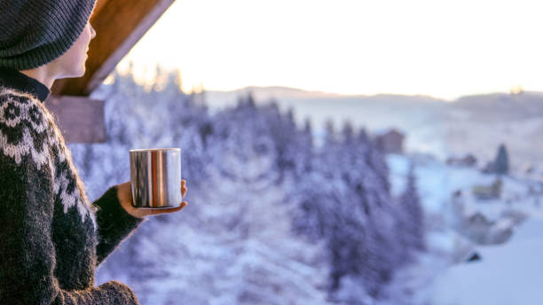 Young woman drinknig coffee with a view of the winter mountain stock photo