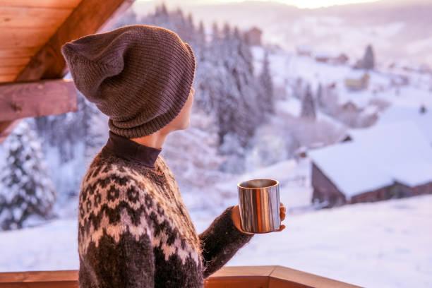 Café do fikar da mulher nova com uma vista da montanha do inverno - foto de acervo