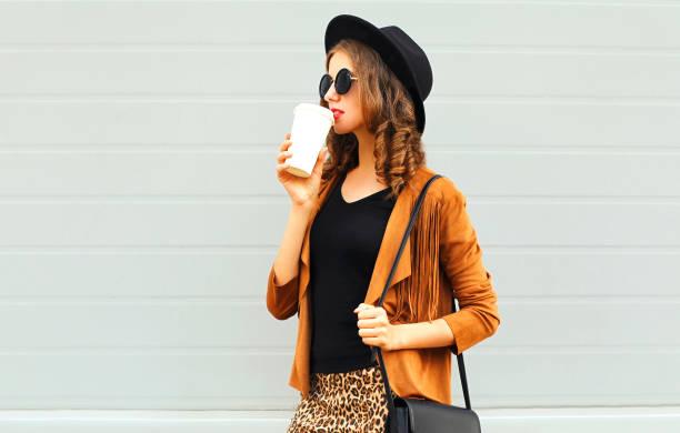 junge frau trinkt kaffee tasse tragen einen retro-eleganten hut, sonnenbrille, braune jacke und schwarze handtasche auf grauem hintergrund - bedruckte leggings stock-fotos und bilder