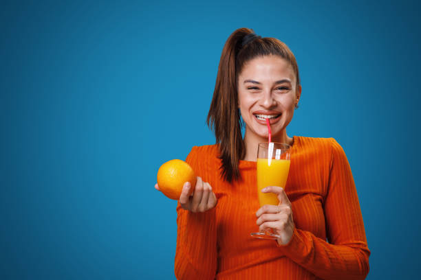 Junge Frau trinkt Orangensaft und hält Orange in der Hand in einem Studio auf blauem Hintergrund – Foto