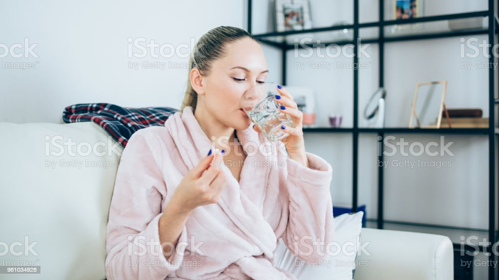 Young woman drinks pills she think about her health stock photo