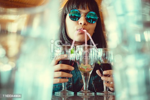 An indoor shoot of Asian/Indian young women in cool round sunglasses. She drinks three glasses of mock-tail drinks at once through straws in a restaurant. The image shot from a low angle through the gap between two blur glasses.