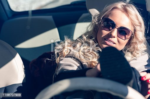 Young woman driver in sunglasses running late struggling to put on her shoes with one foot up on the steering wheel conceptual of inattentiveness and dangerous driving