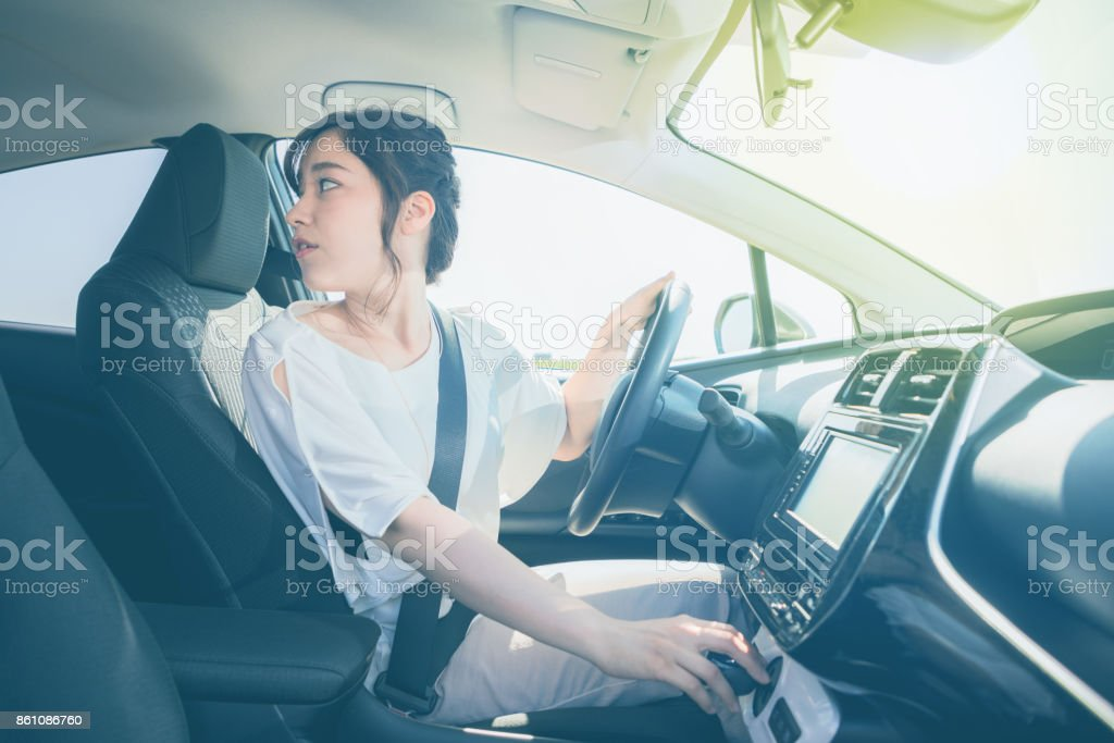 young woman driver turning back. stock photo