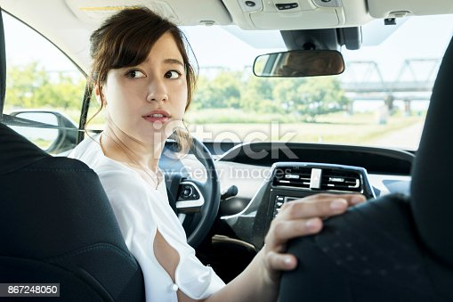 istock young woman driver turning back. 867248050