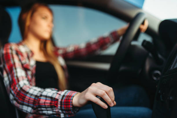 Young woman drives a car stock photo