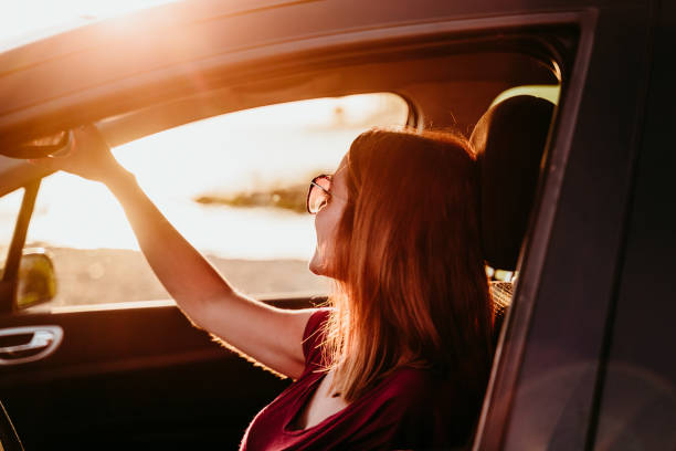 young woman driving a car at sunset. travel concept stock photo