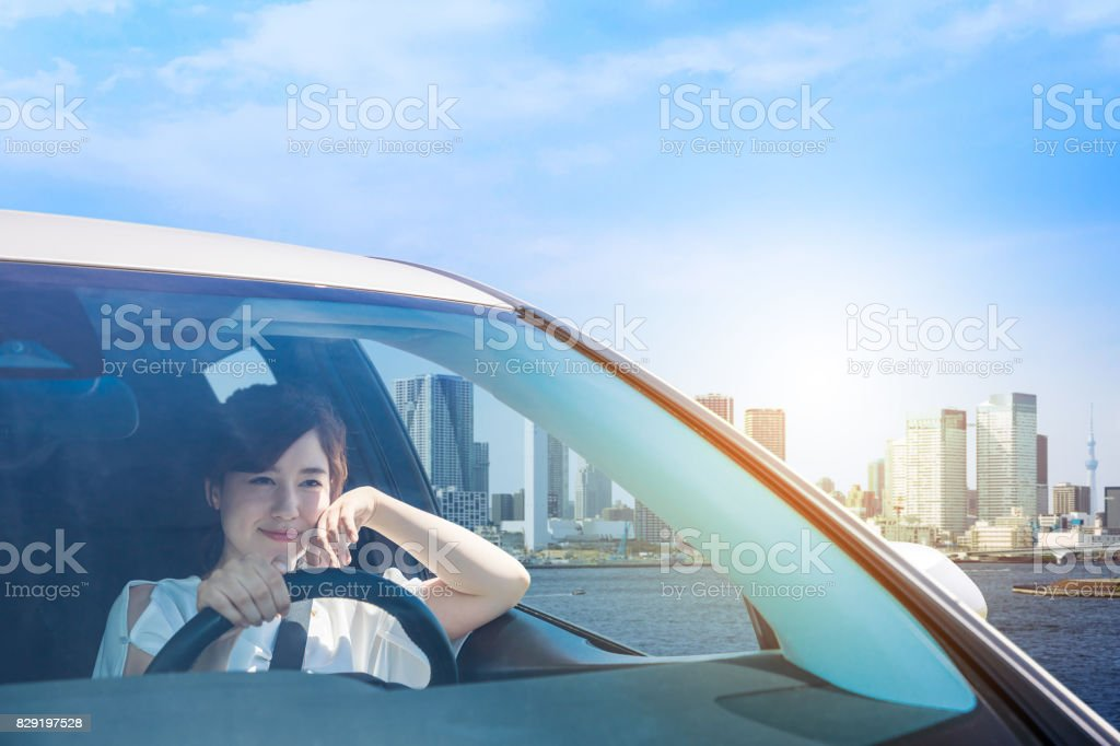 young woman driving a car in the urban city.