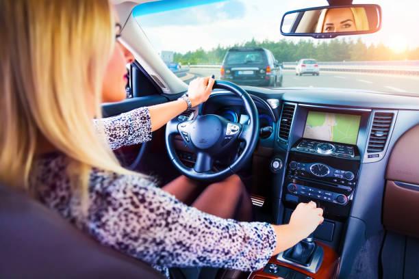 young woman driving a car on a highway - figura femminile foto e immagini stock
