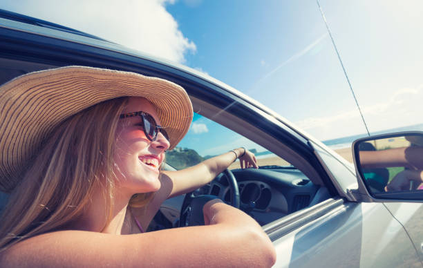 junge frau autofahren am strand. - mietwagen stock-fotos und bilder