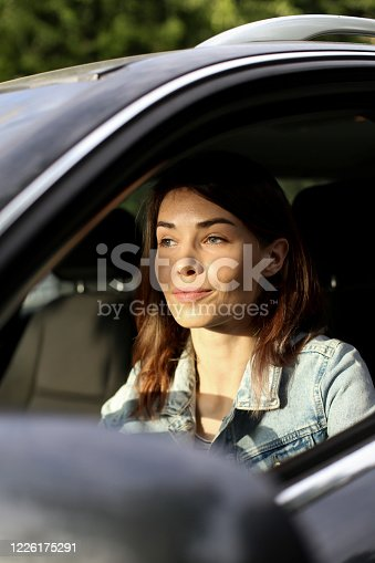 Young woman driving a car. About 25 years old, Caucasian redhead.