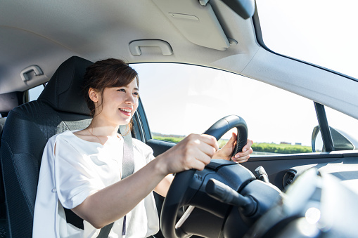 istock young woman driving a car. 894194618