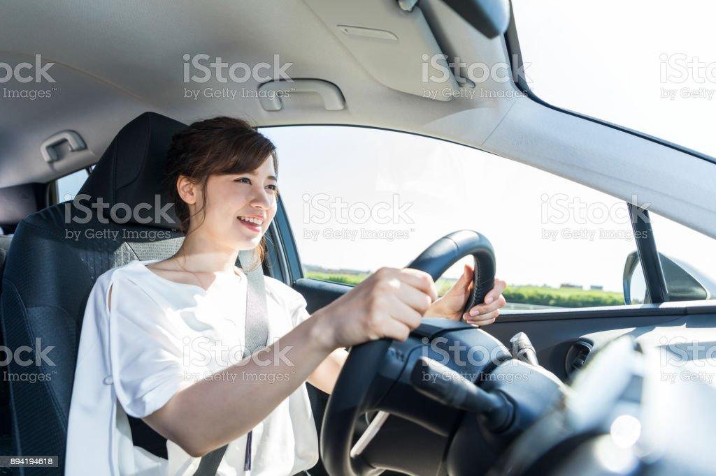 若い女性が車を運転します。 ストックフォト