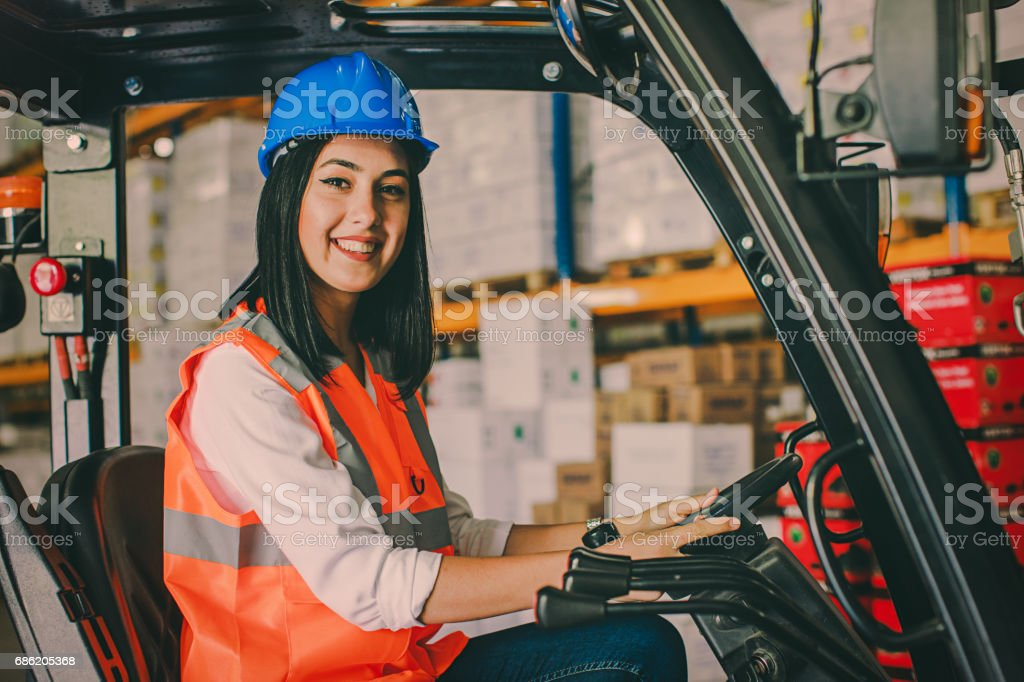 Young woman driving a forklift at warehouse stock photo