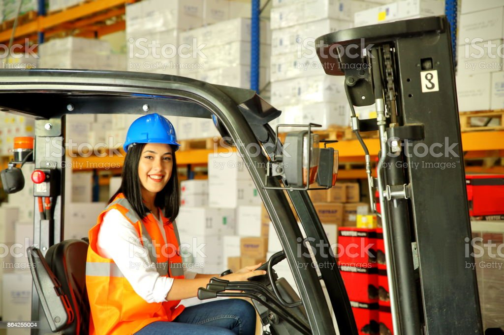 Young woman driving a forklift at warehouse royalty-free stock photo