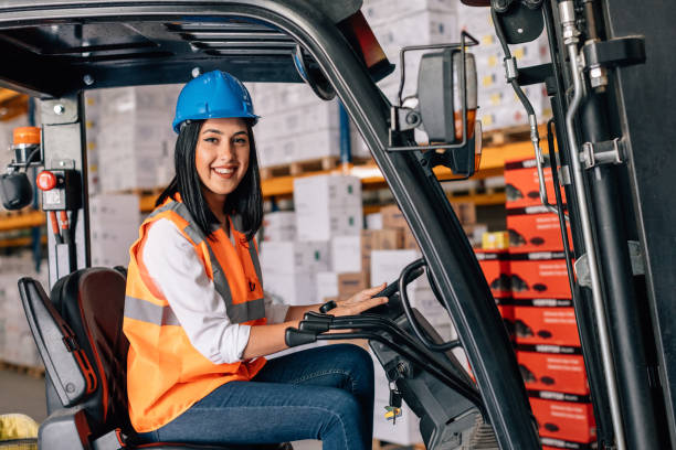 Young woman driving a forklift at warehouse Young happy female forklift driver posing, smiling and driving a worklift at distribution warehouse pallet jack stock pictures, royalty-free photos & images