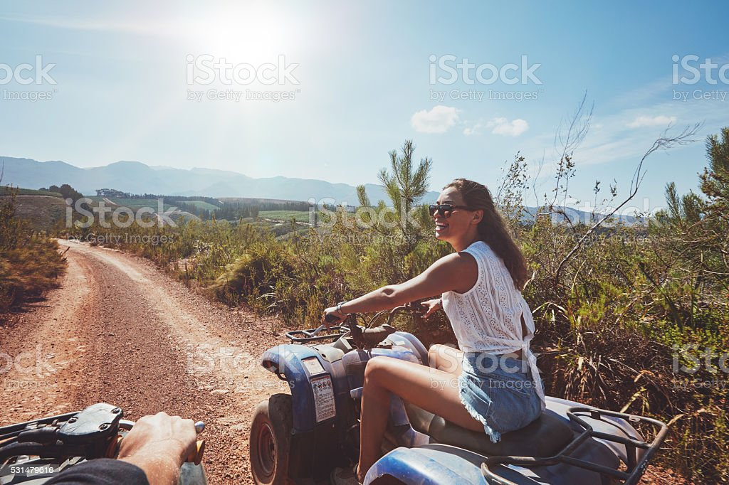 Young woman driving all terrain vehicle in nature stock photo