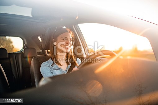 Young woman in a car. She is driving, smiling and looking out. Sun is shining from back on a sunny spring afternoon.