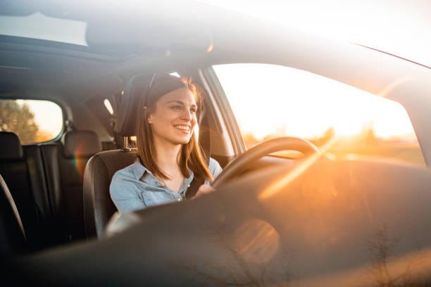 giovane donna alla guida di un'auto in una giornata di sole - auto foto e immagini stock