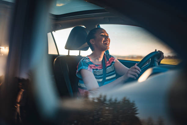 Young woman driving car on a sunny day stock photo