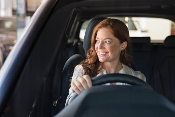 mujer joven conduciendo coche - conducir fotografías e imágenes de stock