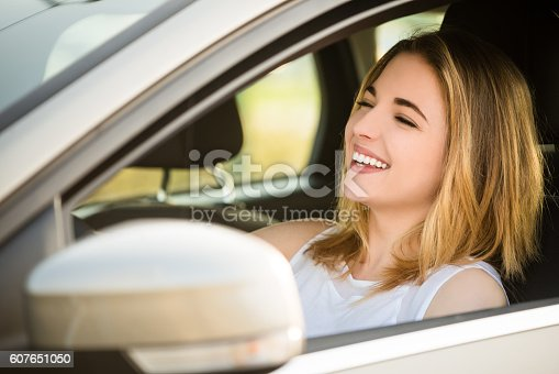 607592606 istock photo Young woman driving car 607651050