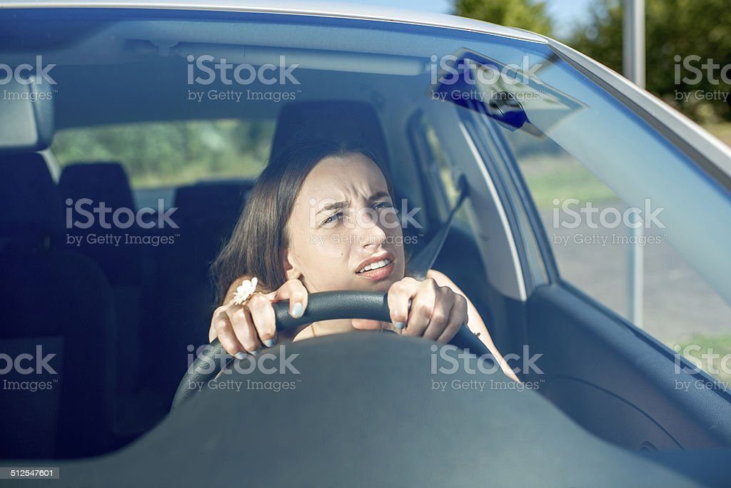 Young woman driving car. Windshield view stock photo