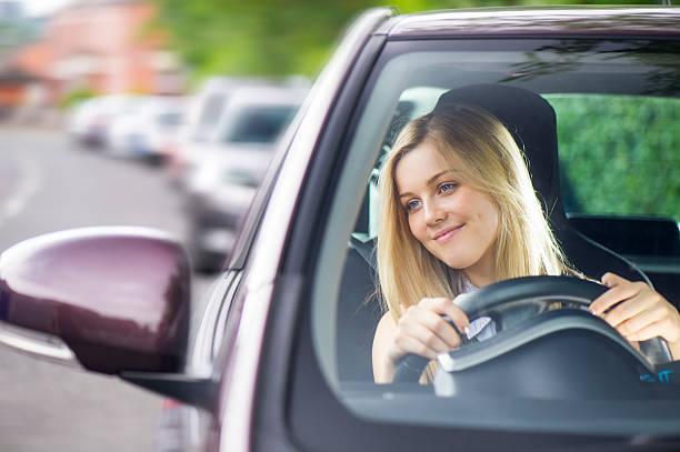 junge frau, die ihr auto fahren - autos für fahranfänger stock-fotos und bilder