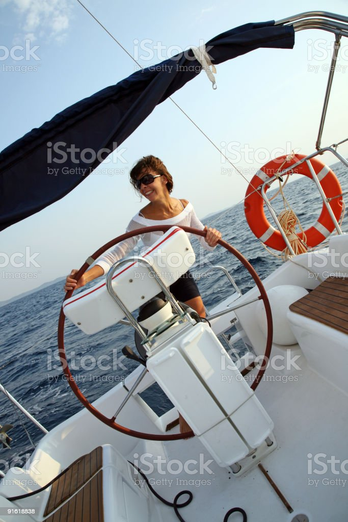Young woman driving the sailboat royalty-free stock photo